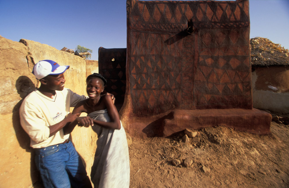 In the chief's compound a modern-dressed Gurunsi teases his brother's wife.  Tiebélé, Burkina Faso