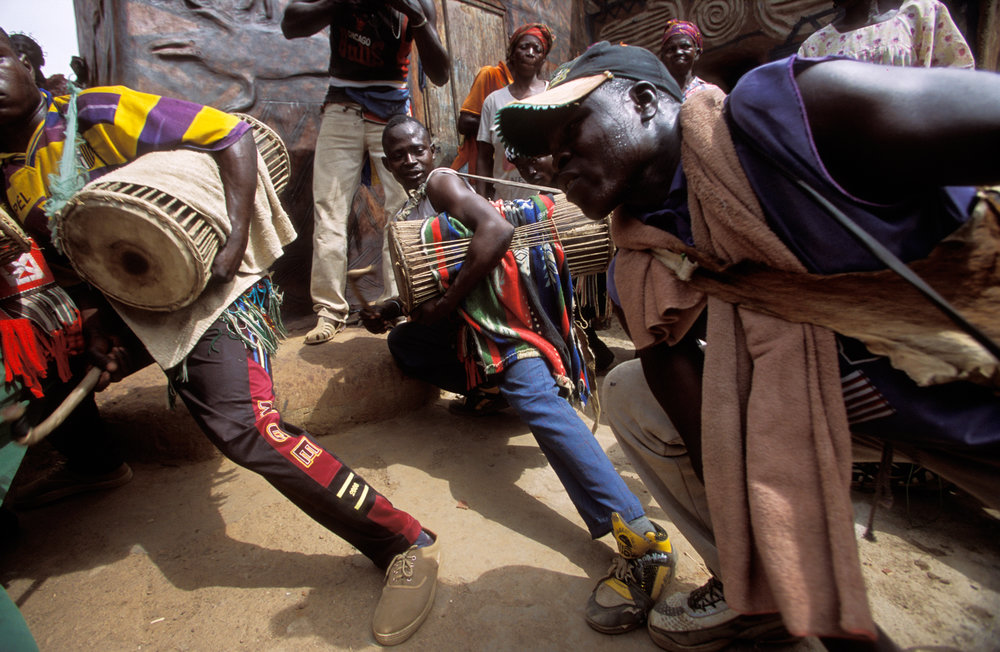 """Gurunsi drummers give a highly charged street performance to start the """"House Painting Day"""", which is part of the Tiebélé arts festival.  Tiebélé, Burkina Faso"""