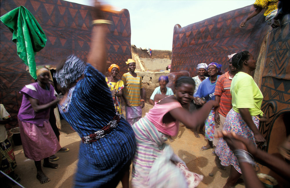 """During the mural competition in Tiebélé, the Gurunsi women of Burkina Faso take a break to dance, sing, and do """"the bump.""""  Tiebélé, Burkina Faso"""