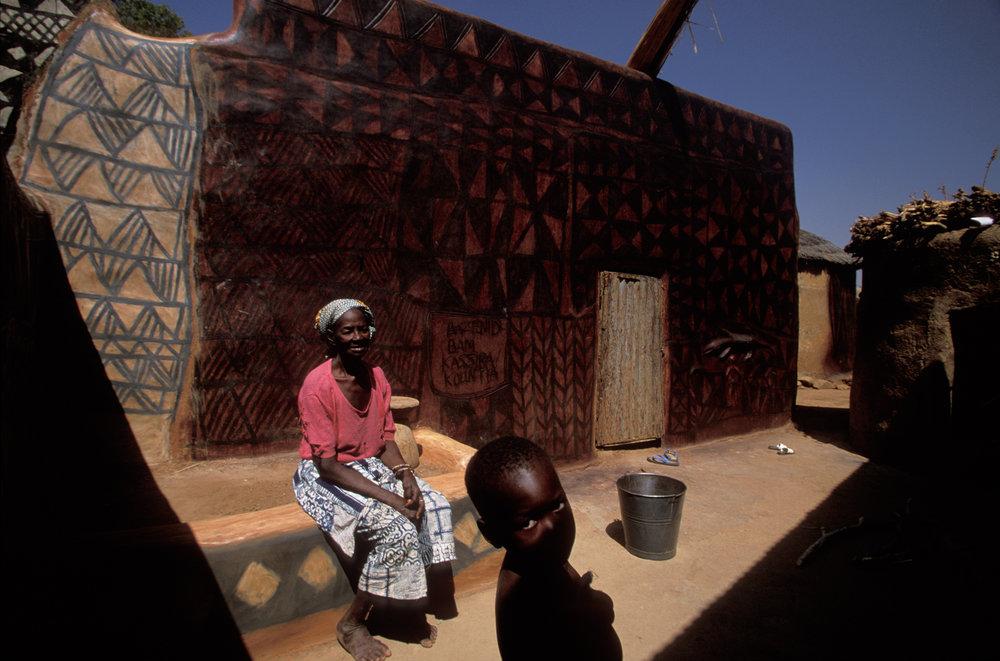An elderly Gurunsi woman enjoys the sight of the newly painted houses in her hometown Tiebélé.  Tiebélé, Burkina Faso