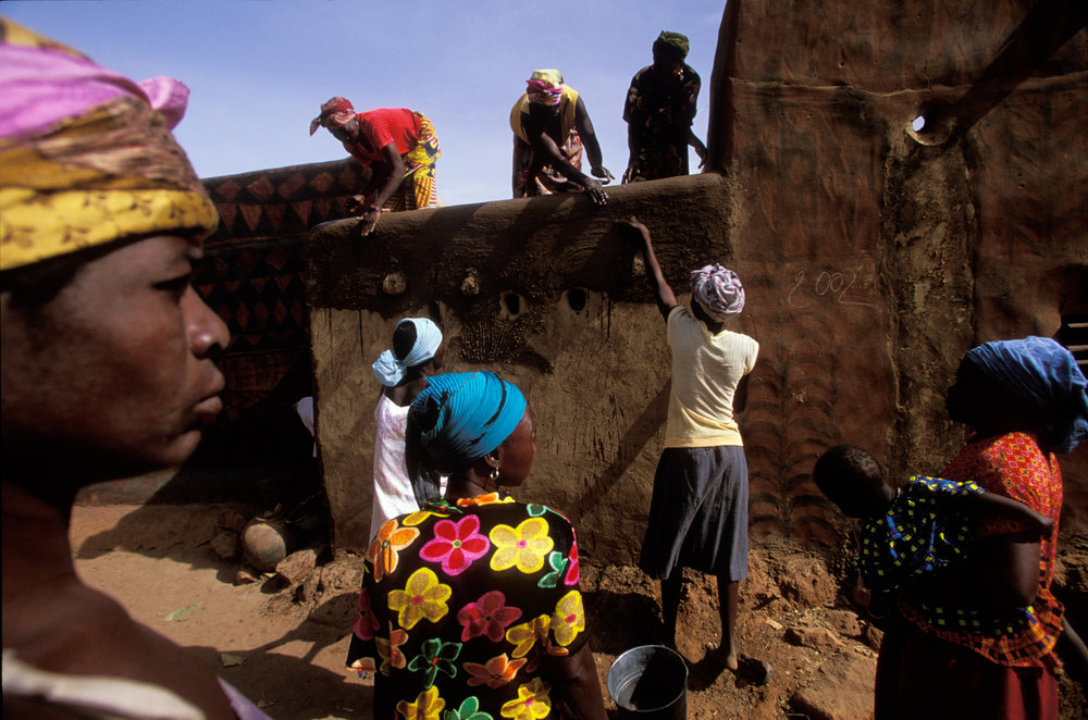 Once a year, during the annual art and culture festival, houses are repainted with beautiful designs. Women first coat the compound's walls with a fresh layer of clay before painting.  Tiebélé, Burkina Faso