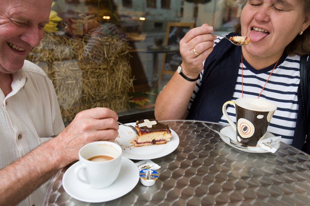 A tourist couple enjoys a new Marktl pastry - layered marzipan (a Pope Benedict XVI favorite) glazed with chocolate and topped with a marzipan cross.  Marktl, Germany