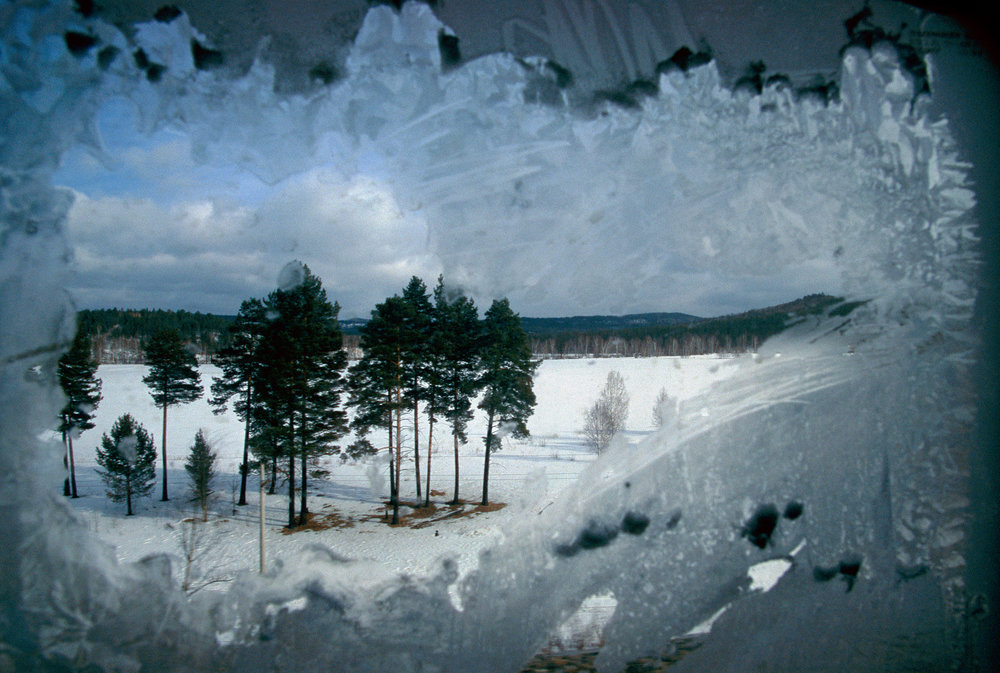 Endless trees and the frozen silence of the Russian taiga slide past the frosted window of the Trans-Siberian Railroad as it sweeps east of Lake Baikal.  Siberia, Russia