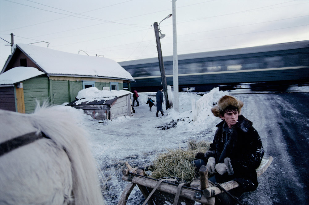 Villagers in the Siberian taiga take little notice as a train hurtles by. Many still rely on a time-honored mode of transportation – horse-drawn sleighs.  Svishchevo, Russia