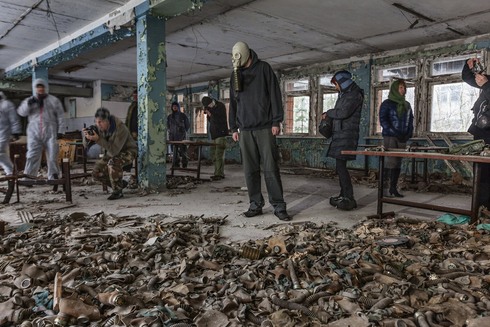 One tourist brought his own gas mask, not to protect himself from the radiation - but simply for photographs and giggles.  Pripyat, Ukraine