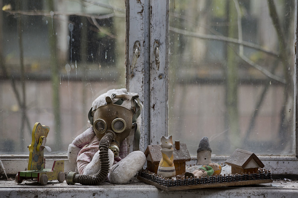 In an abandoned kindergarten children's toys and gas masks create a strange still life. One can suspect that the mix was created intentionally.  Pripyat, Ukraine