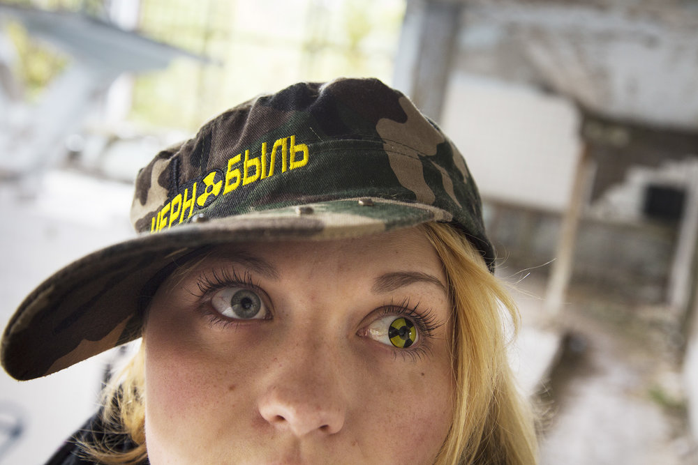 A tour guide sets the off-beat tone for the tourists with a Chernobyl hat and contact lens in the shape of a radiation symbol.  Pripyat, Ukraine
