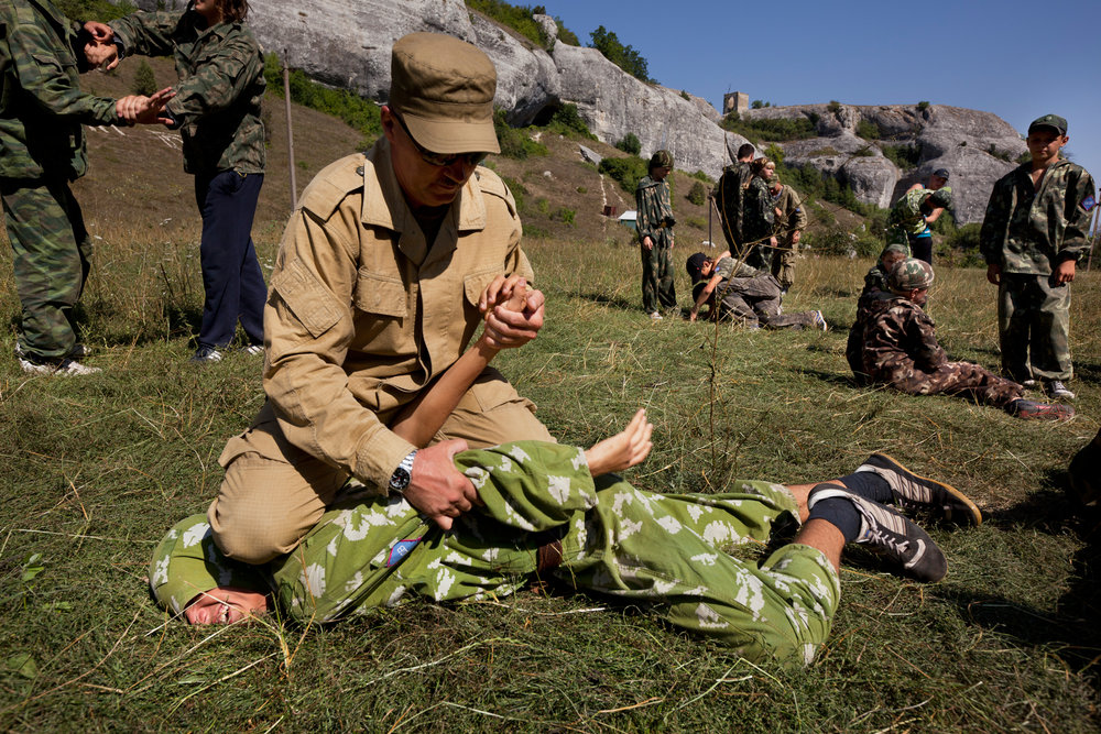 An instructor demonstrates disarming an armed enemy on of of the young boys.  Eski-Kermen Region, Crimea