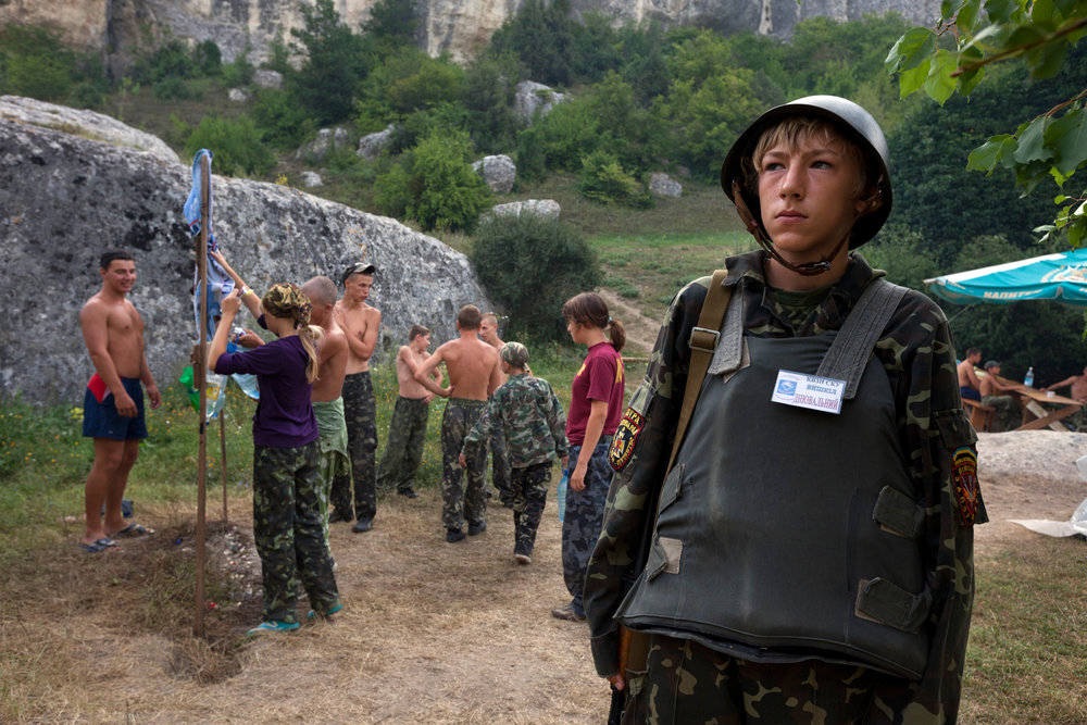An armed child patrols the entrance to a camp for children aged 8-16, while his peers take care of their morning hygiene.  Eski-Kermen Region, Crimea
