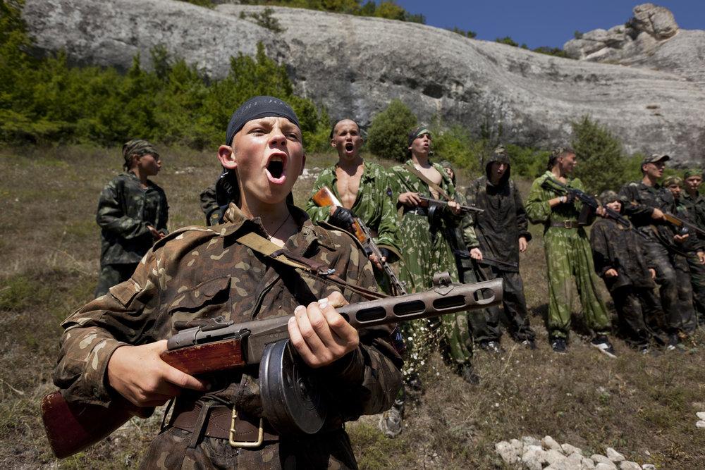 Holding a machine gun, a young boy calls out before a drill.  Eski-Kermen Region, Crimea