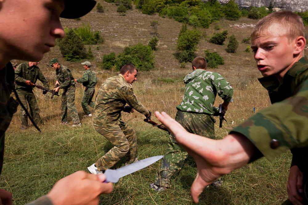 Practicing an ambush, children learn to defend themselves against an enemy using knifes.  Eski-Kermen Region, Crimea