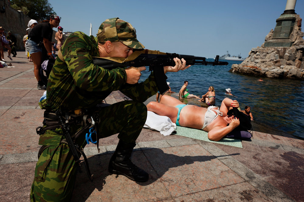 Tourists casually sunbathe at the Sevastopol embankment as members of the Black Sea Fleet rehearse their military show for the upcoming Day of the Russian Fleet.  Sevastopol, Crimea