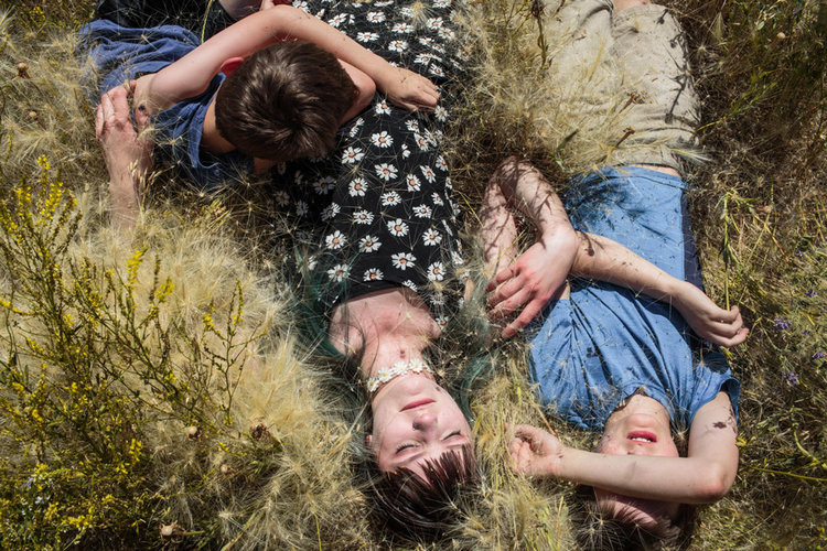 """We dream of the past like some people dream of the future."" Rebekah Engebretson Curtis, Kate and Jude, all of whom are homeschooled, lay in their   backyard in Watford, North Dakota, on a dry, hot summer afternoon. © Sarah Blesener, 2018 Smith Fellowship Recipient"