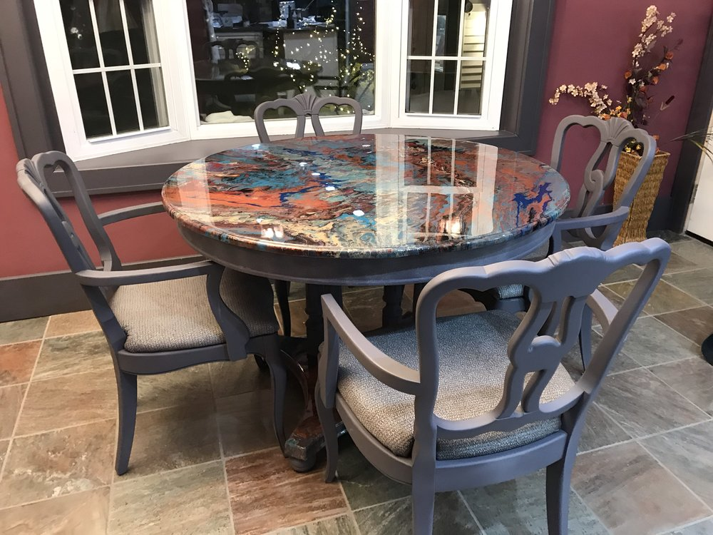 """Dining Table & Chairs  >Table top is is painted with an acrylic pour and sealed with an epoxy resin.  > Chairs are upholstered with a """"wipeable"""" fabric and arms were handcrafted and added to chairs.  >Table and chars are solid wood."""