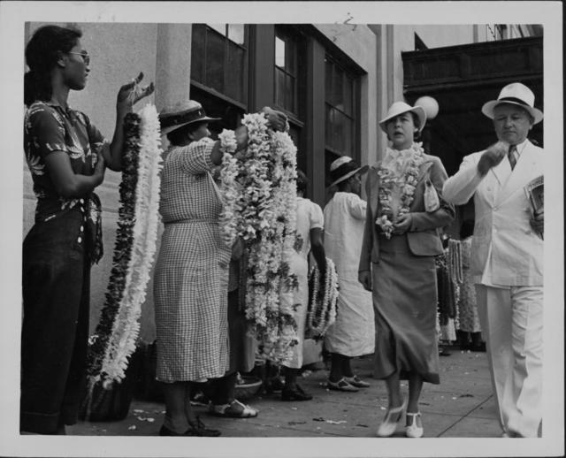 Lei vendors selling to passengers disembarking from cruise ships during the 1930's.  Source: Hawaiʻi State Archives Digital Collection.