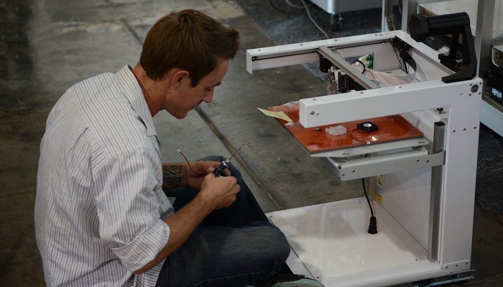 Technician-on-ground-with-3D-printer-repair-machine.jpg