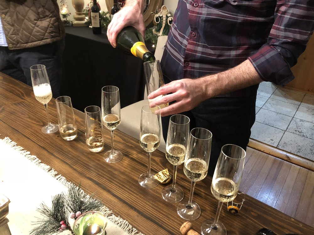 Nine Champagne Glasses filled with Veuve for Nine Good Friends ringing in the new year like grown adults.
