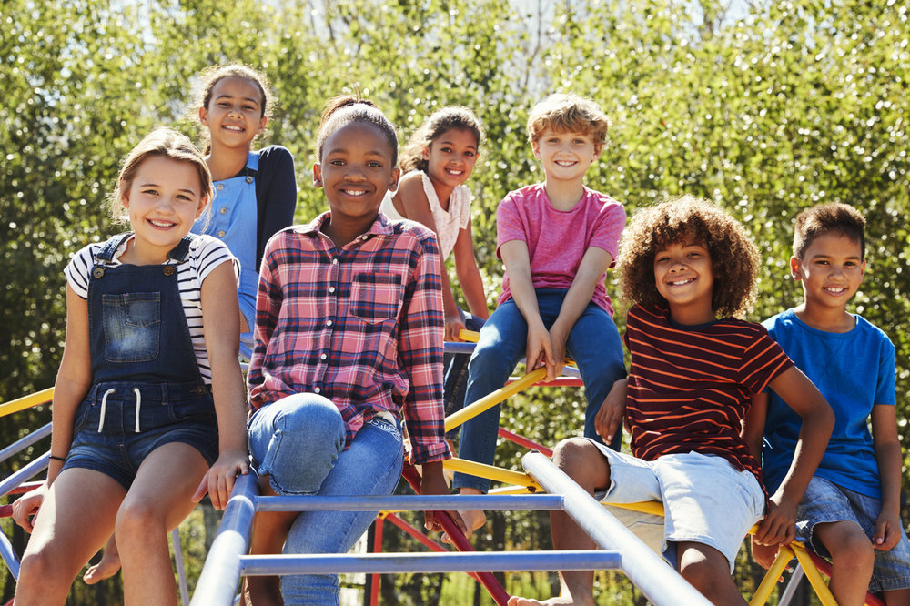 Pre-teen-friends-sitting-on-climbing-frame-in-playground-839296132_1258x838.jpeg
