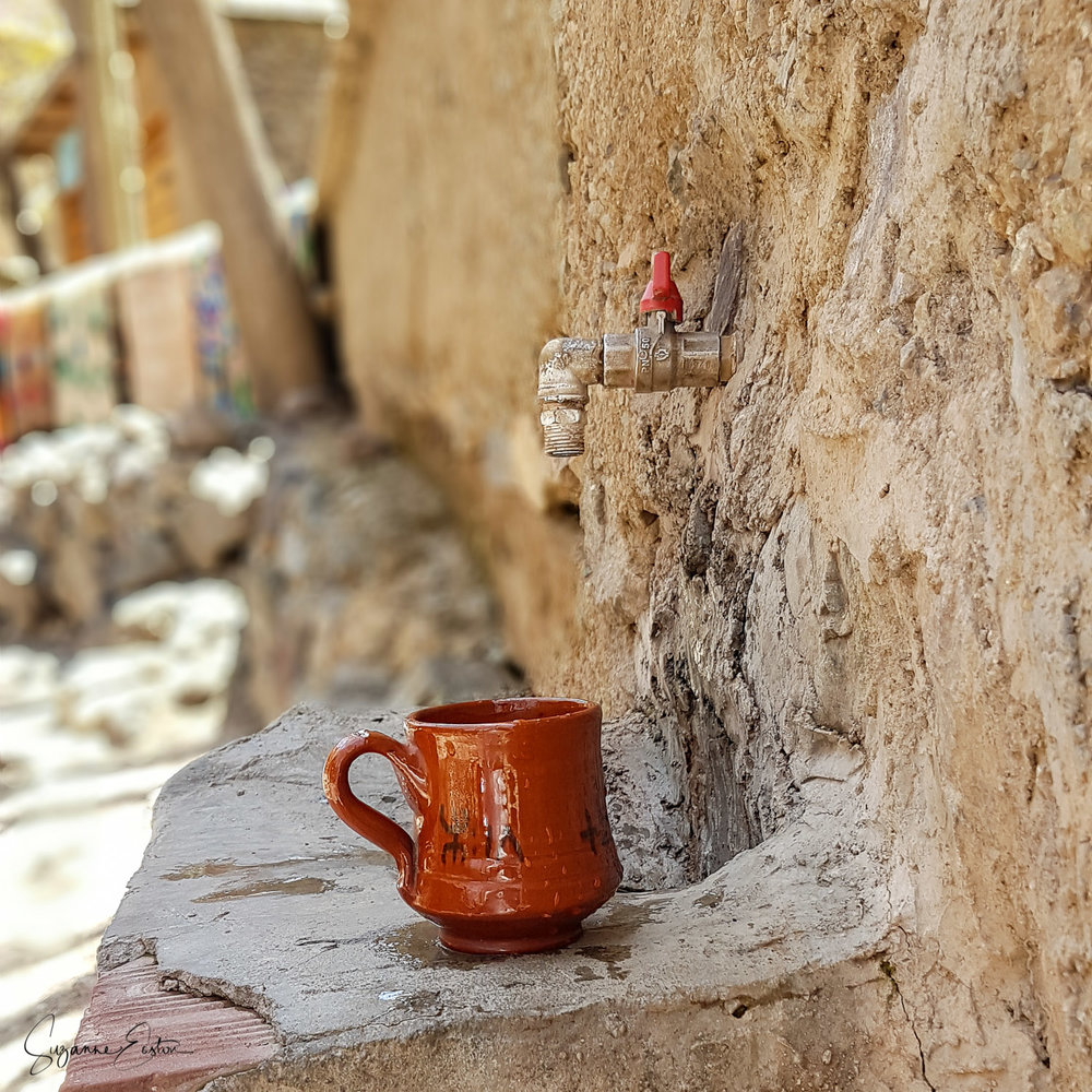 A mug left beside a tap on the side of a mountain in Morocco.