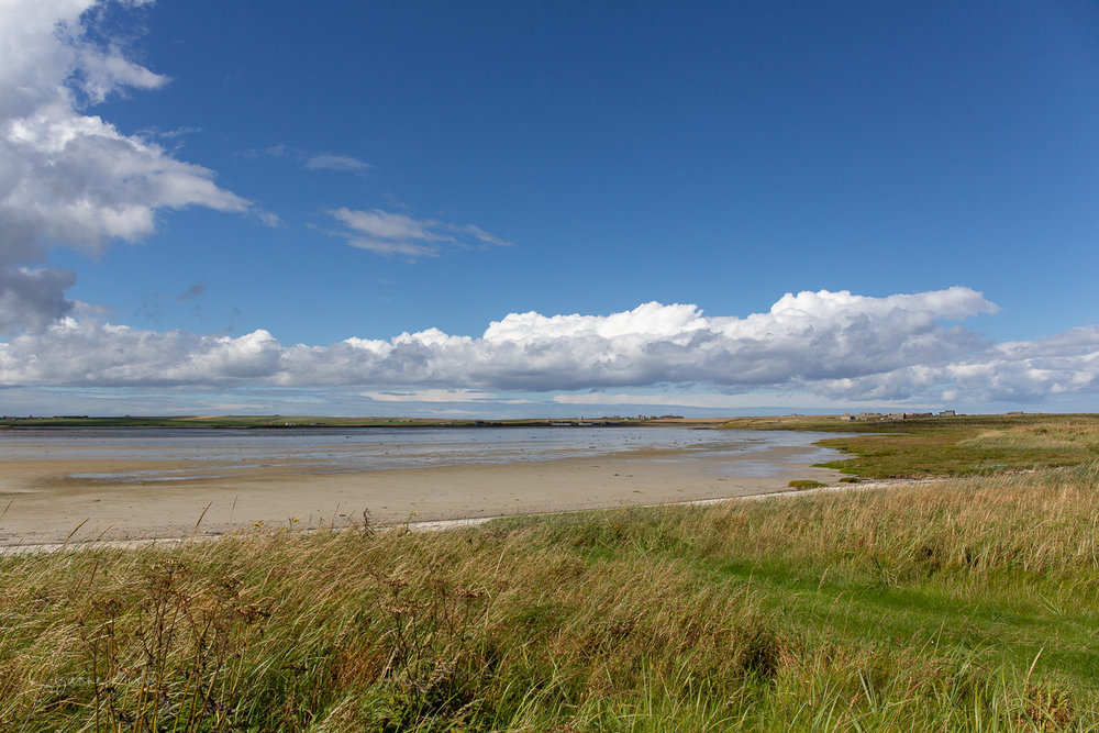 Peedie Sea on Sanday with blue sky and clouds.