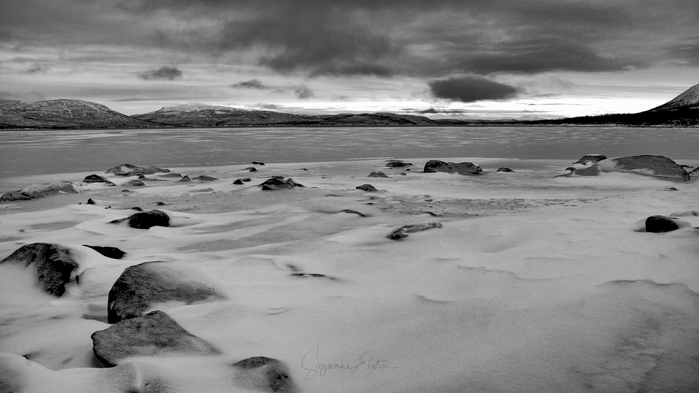 A lake in Sweden with snow in black and white