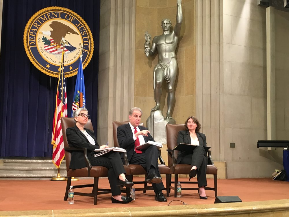 Inspector General Michael Horowitz speaks to DOJ employees on the stage of the Main Justice building along side Stacey Young (L) and Colleen Phillips (R)