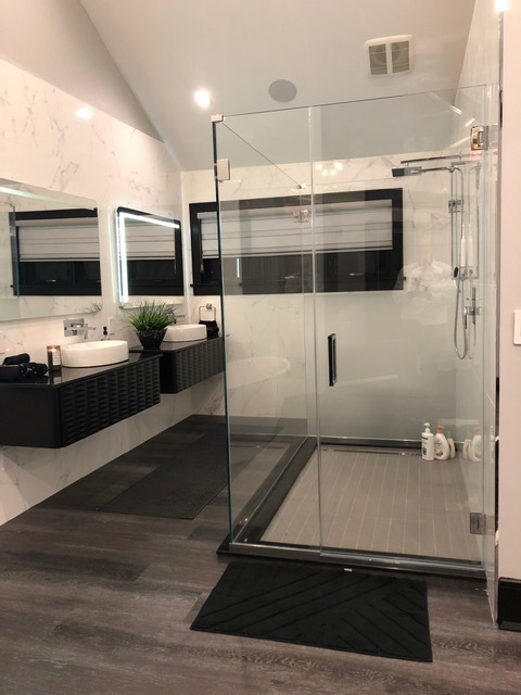 Modern floating vanities and a large shower sit on porcelain tiles