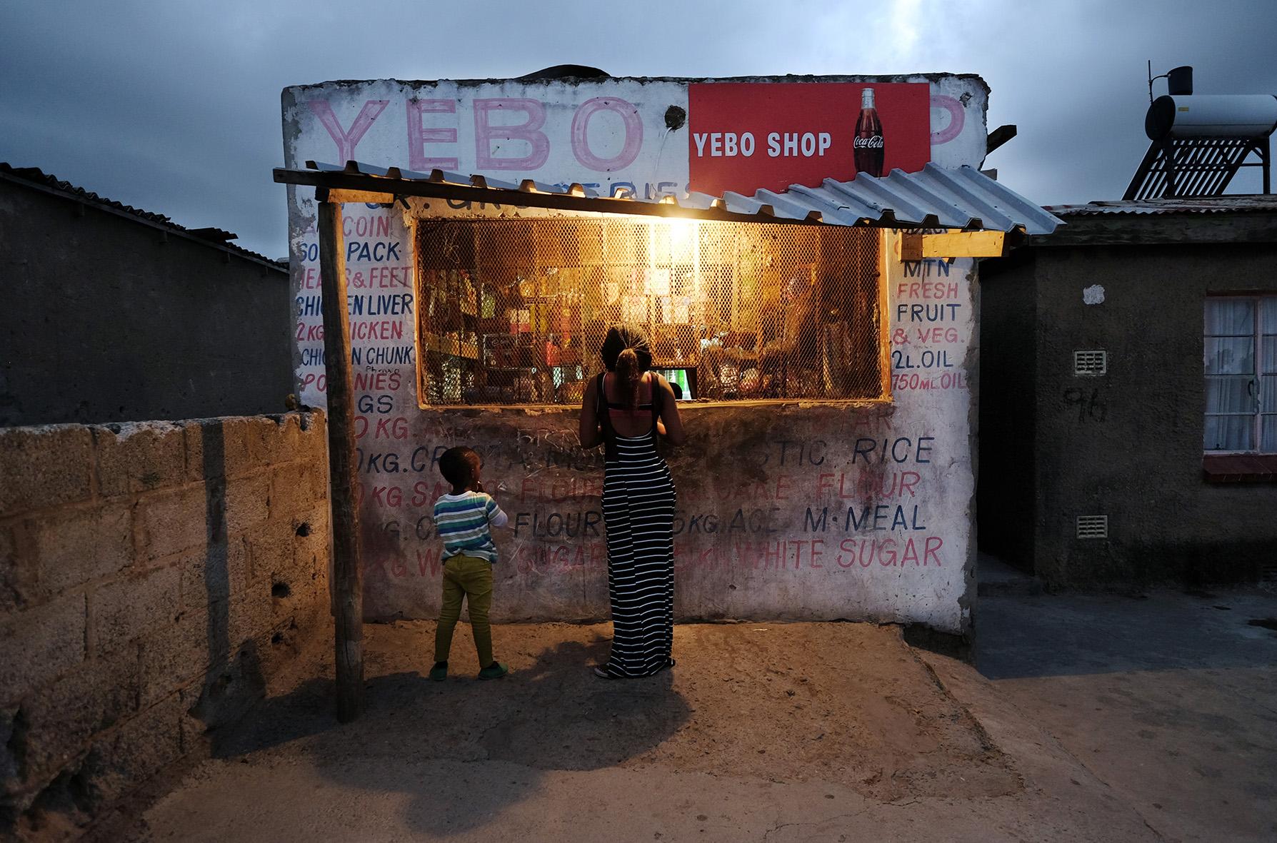 Foto gemaakt in een township (New Brighton township) in Port Elisabeth, Afrika. Moeder met kind koopt iets aan een kraam. Alles is achter slot en grendel in die gevaarlijke townships. Eind februari 2015 © An-Sofie Kesteleyn