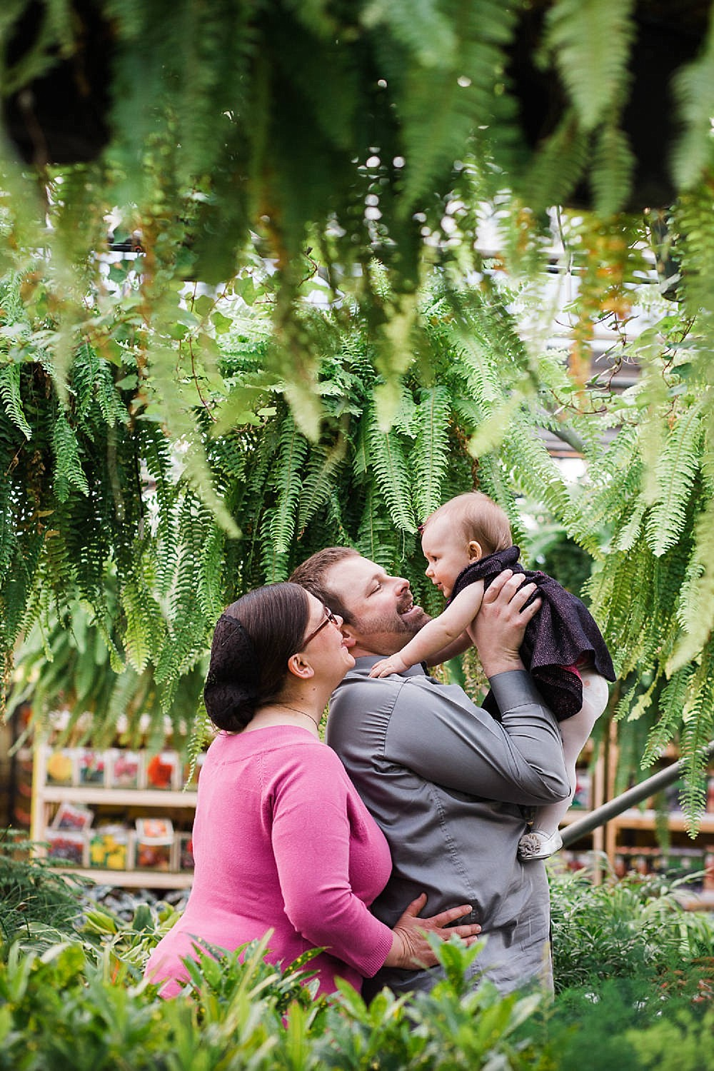 Mother and Father holding up their baby girl in a greenhouse.