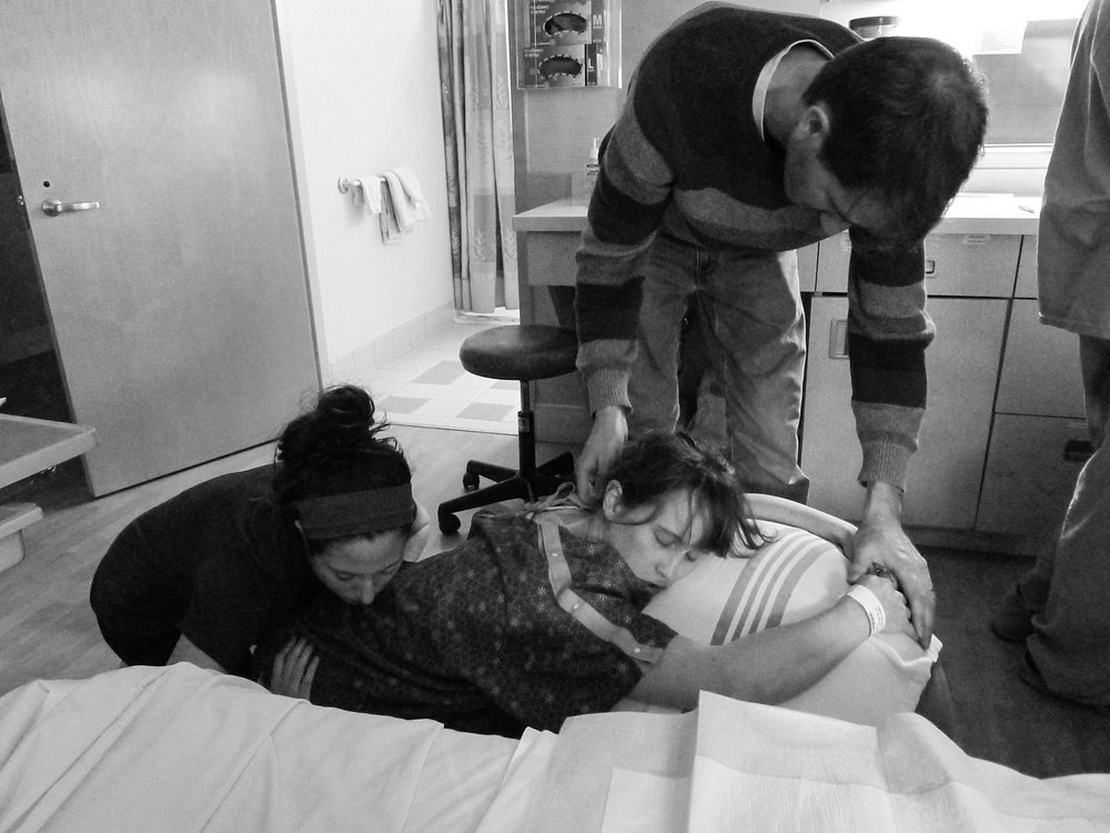 Woman in labor at the hospital, surrounded by her husband, doula and nurses.