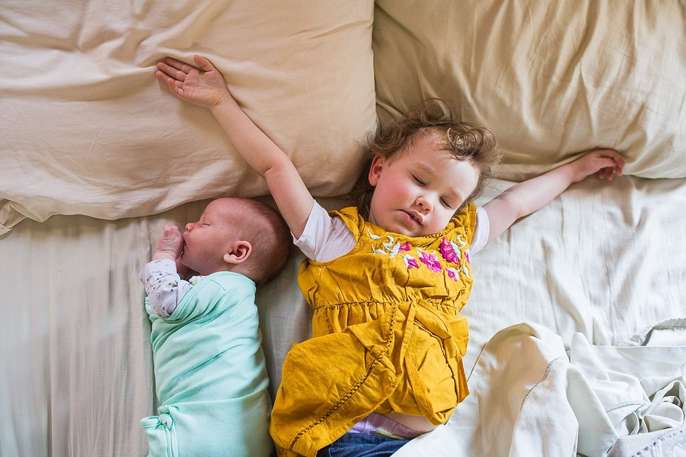 Photo of a newborn baby and his toddler big sister napping together in bed.