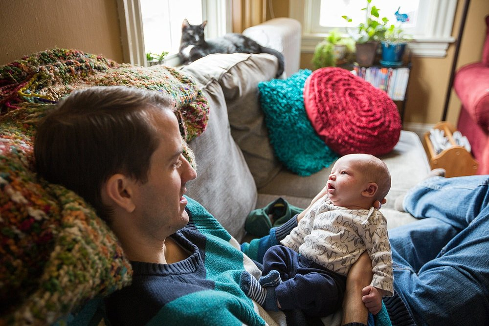 Photo of a father holding his newborn baby boy on the couch in their home.