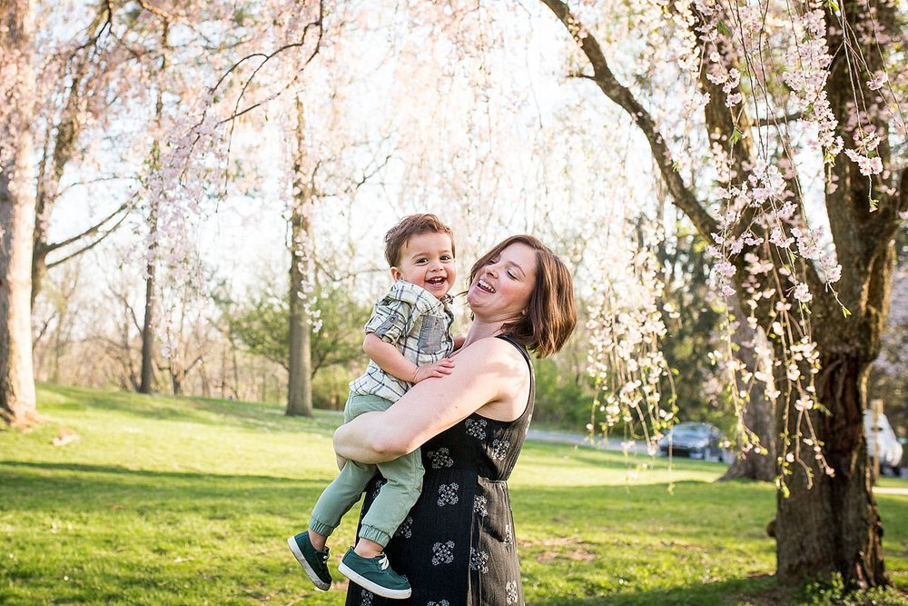 Happy photo of a mother holding her toddler son in front of a flowering cherry tree at Buchmiller Park.
