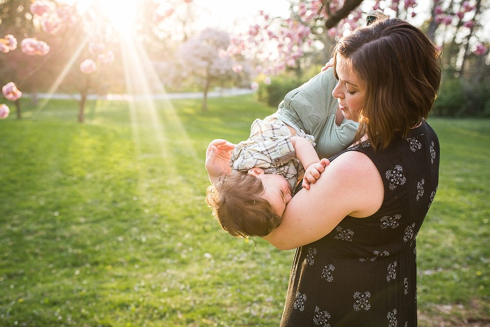 Happy photo of a mother holding her toddler son in front of a flowering cherry tree at Buchmiller Park with the sunlight shining in the background.