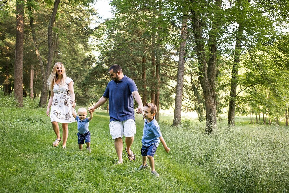 Photo of a family of four walking down a path in the woods.