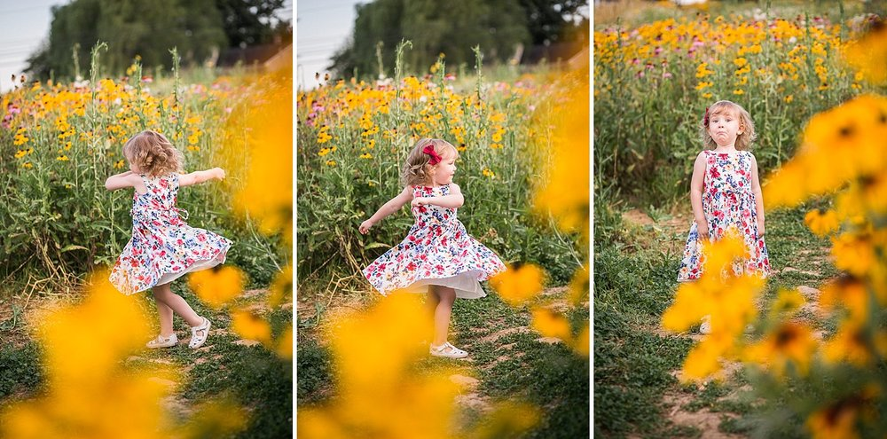 A little girl wearing a flowered dress twirls in a field of yellow wildflowers.