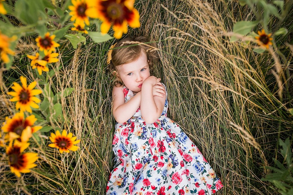 A little girl wearing a flowered dress lies in a field of yellow wildflowers.