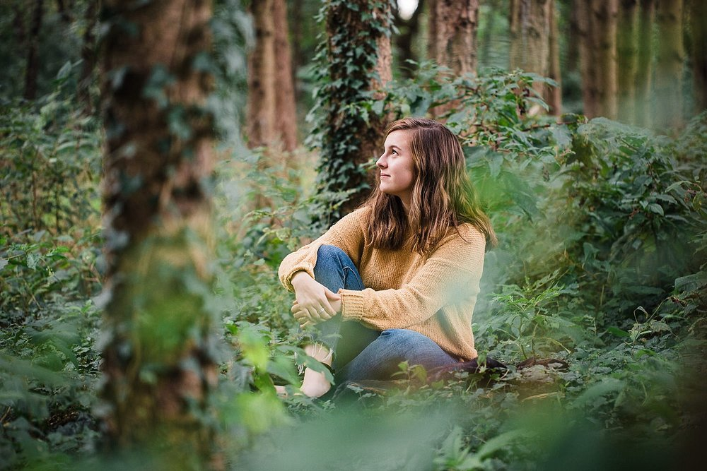 Lancaster senior session photo of a young girl in a yellow sweater and jeans sitting in a pine forest.