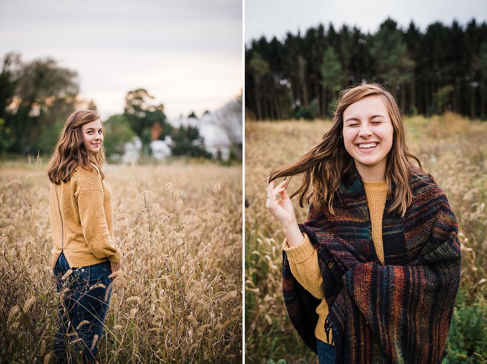 Lancaster senior session photo of a young girl with brown hair wearing a yellow sweater and striped blanket standing in a field of golden grasses.