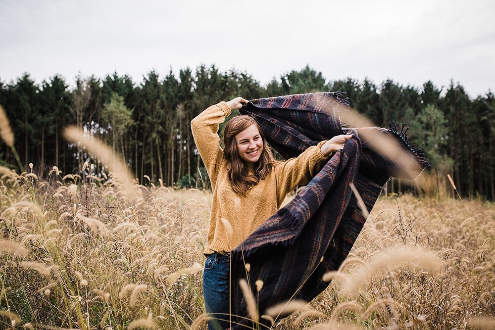 Young woman wrapped in a blanket standing in a field of golden grasses.