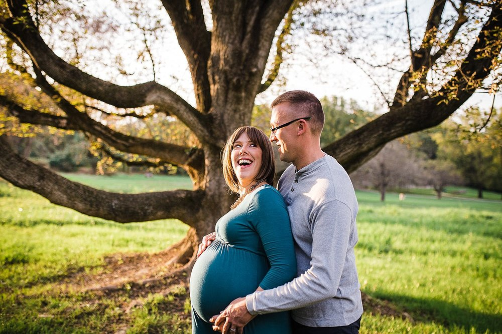 Photo of a pregnant woman and her husband smiling in the golden sunlight