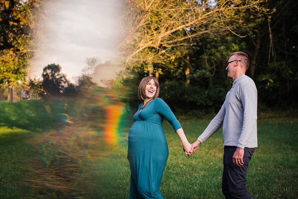 Photo of a pregnant woman and her husband walking down a path hand in hand.