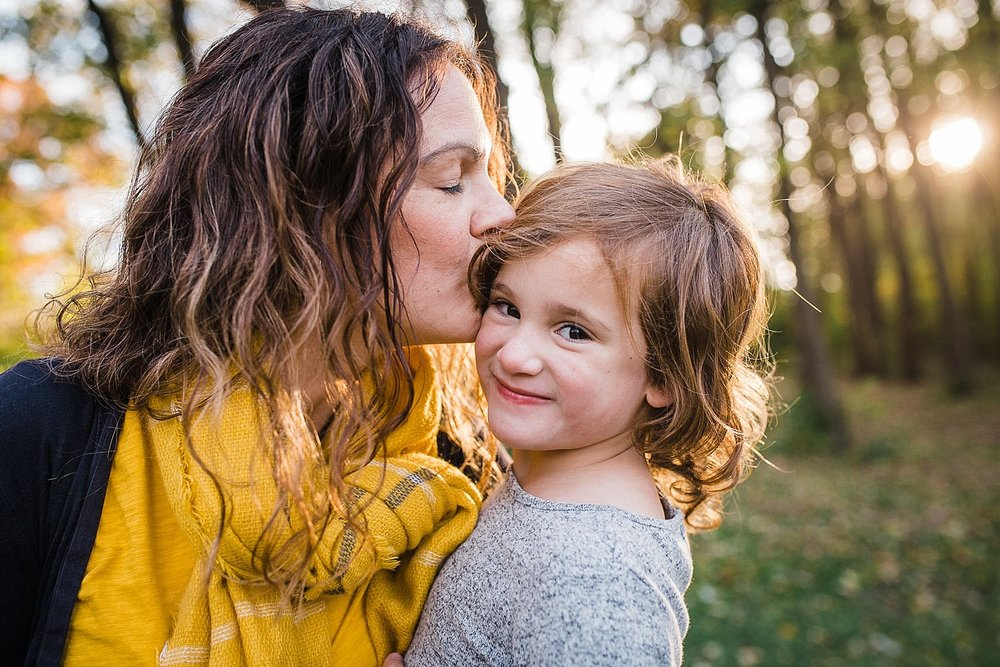 Photo of a mother kissing her daughter in the golden fall light.