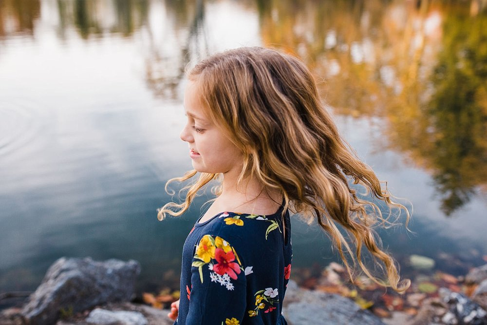 Photo of a girl with long wavy hair standing in front of a pond with golden fall leaves in the reflection