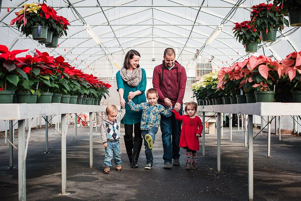 Photo of a family of five walking through a greenhouse with poinsettias on both sides.