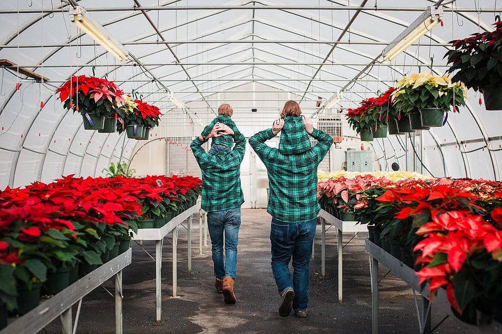 Photo of two dads walking through a greenhouse with kids on their shoulders at Christmas time.