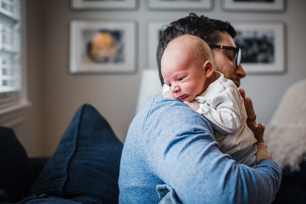 Photo of a young father holding his newborn son on a blue sofa in his home.