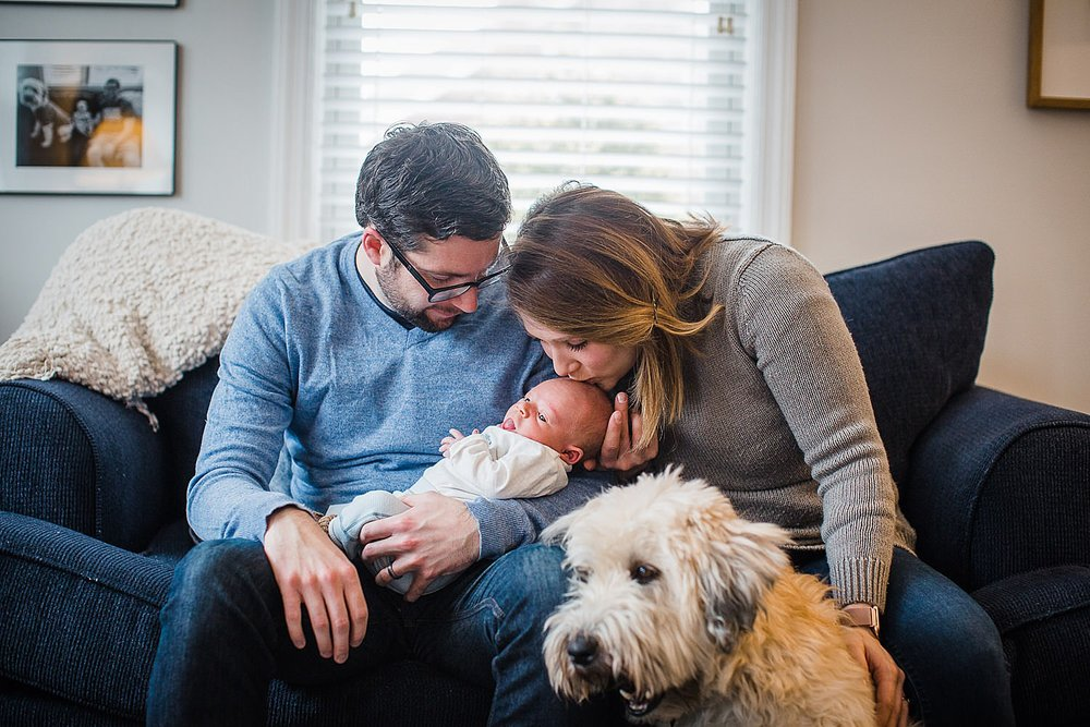 Photo of a mother and father holding their newborn son in their home with a shaggy dog in the foreground.