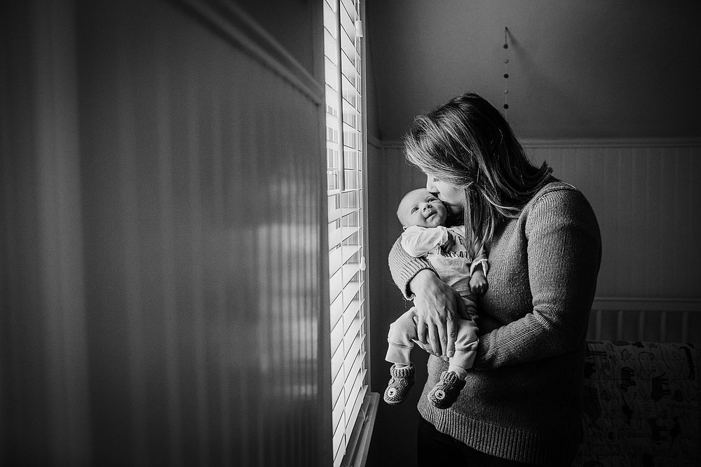 Photo of a mother kissing her newborn son in the nursery next to the window.