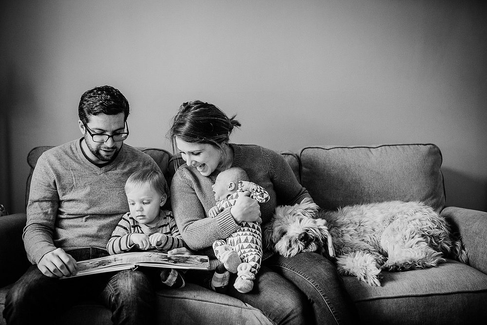 Photo of a young family reading a book together on the couch.